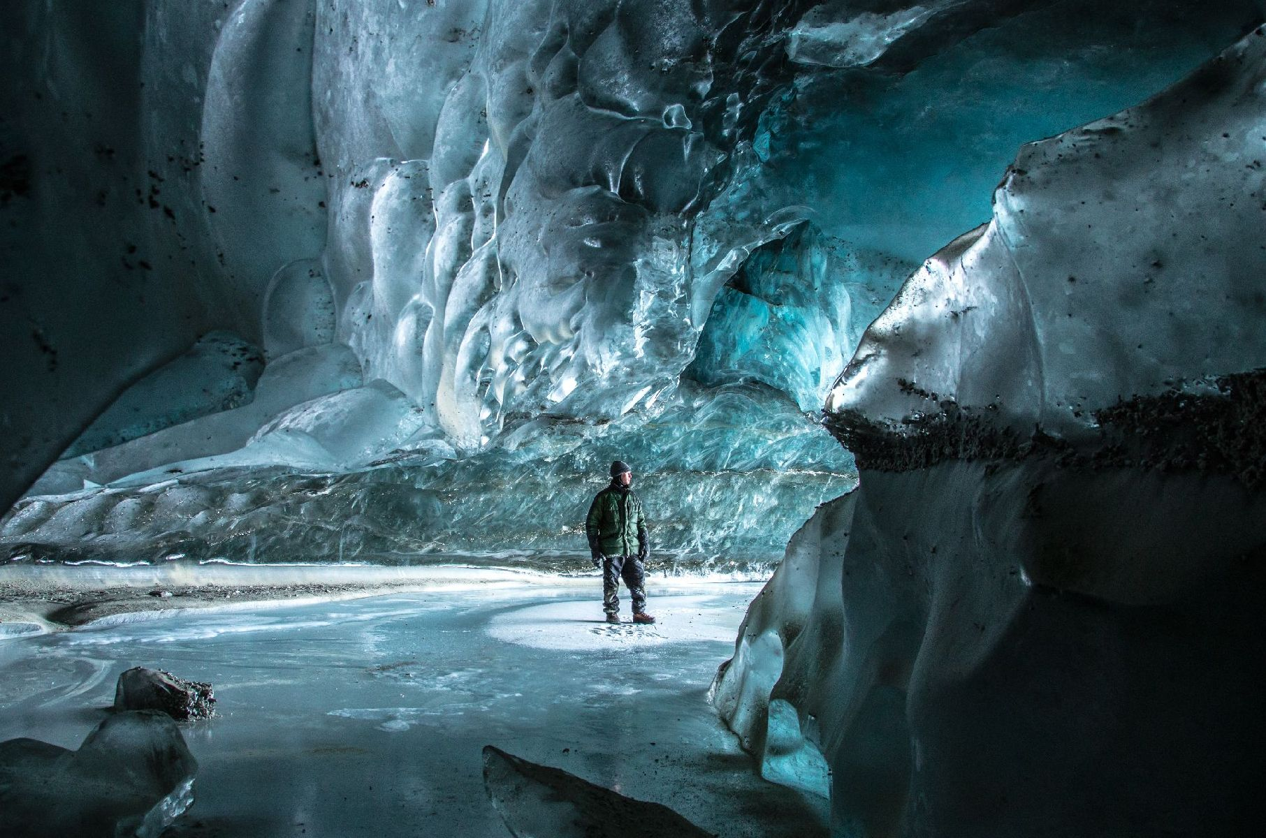 Exploring an ice cave in Canwell Glacier after snowshoeing two miles from the Richardson Highway on