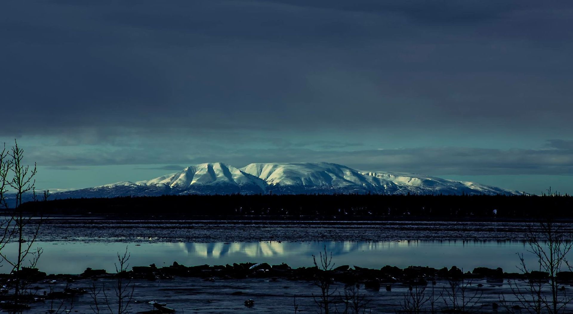 Mount Susitna also known as The Sleeping Lady under a dark layer of clouds. The mountain is located