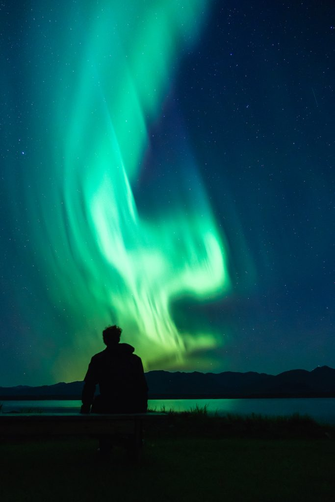 Man stands silhouetted under a green ribbon of aurora near Lake Clark in Alaska.