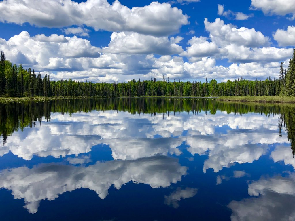 Clouds reflect on the surface of a calm lake.