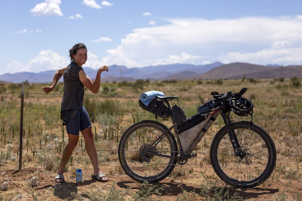 Lael Wilcox poses flexing by her bicycle at the finish of the Tour Divide route