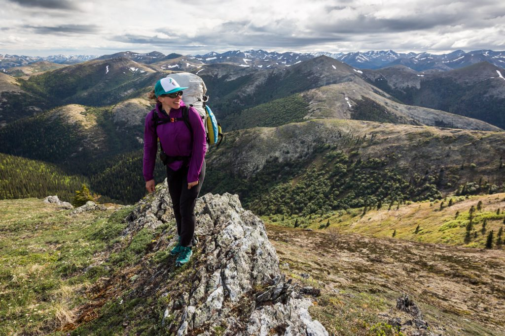Woman backpacker looks over her should with Nulato HIlls behind