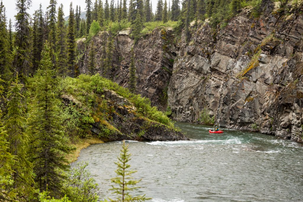 Packrafting down North River past steep cliff