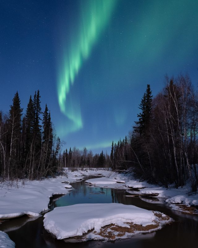 Northern Lights over a snowy river