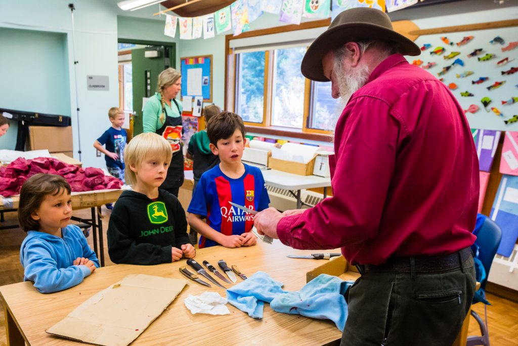 Older volunteer teaches knife sharpening on moose butchering day
