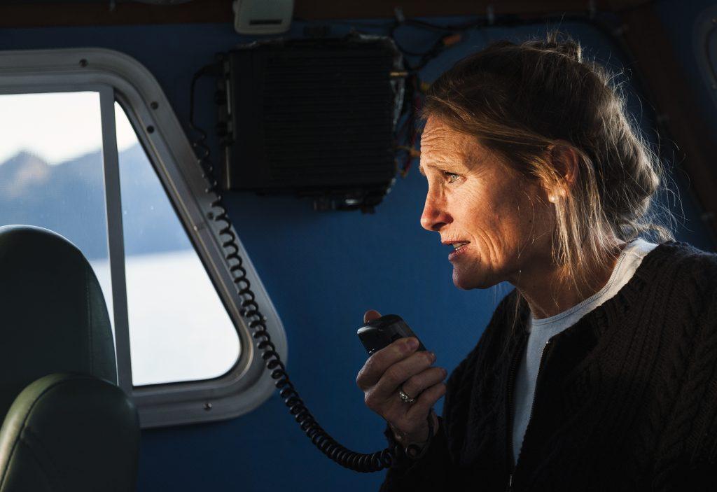 Female skipper talks into the boat radio
