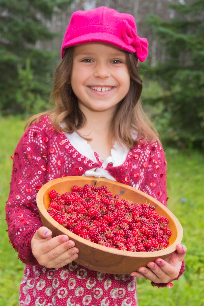 Seven-year-old girl smiles and holds a bowl of red nagoonberries.