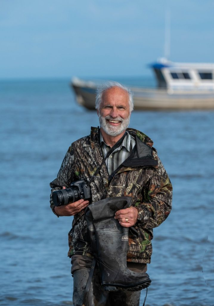 Man wearing a camo jacket and carrying a camera walks to shore with a boat in the background.