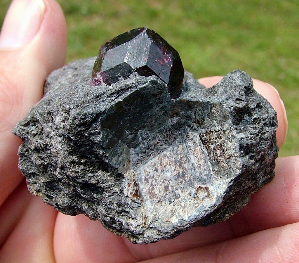 A black stone embedded in a dark rock held in someone's hand