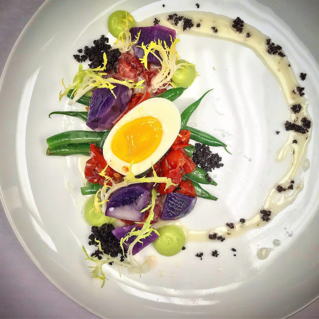 A white plate decorated lavishly with food
