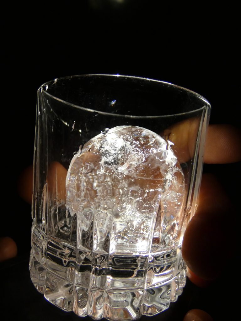 Rocks glass with a round, clear glacial ice cube