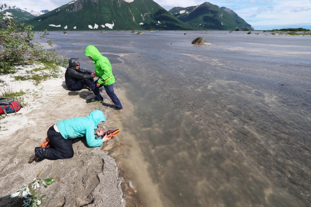 Hikers wash their shoes in Katmai River