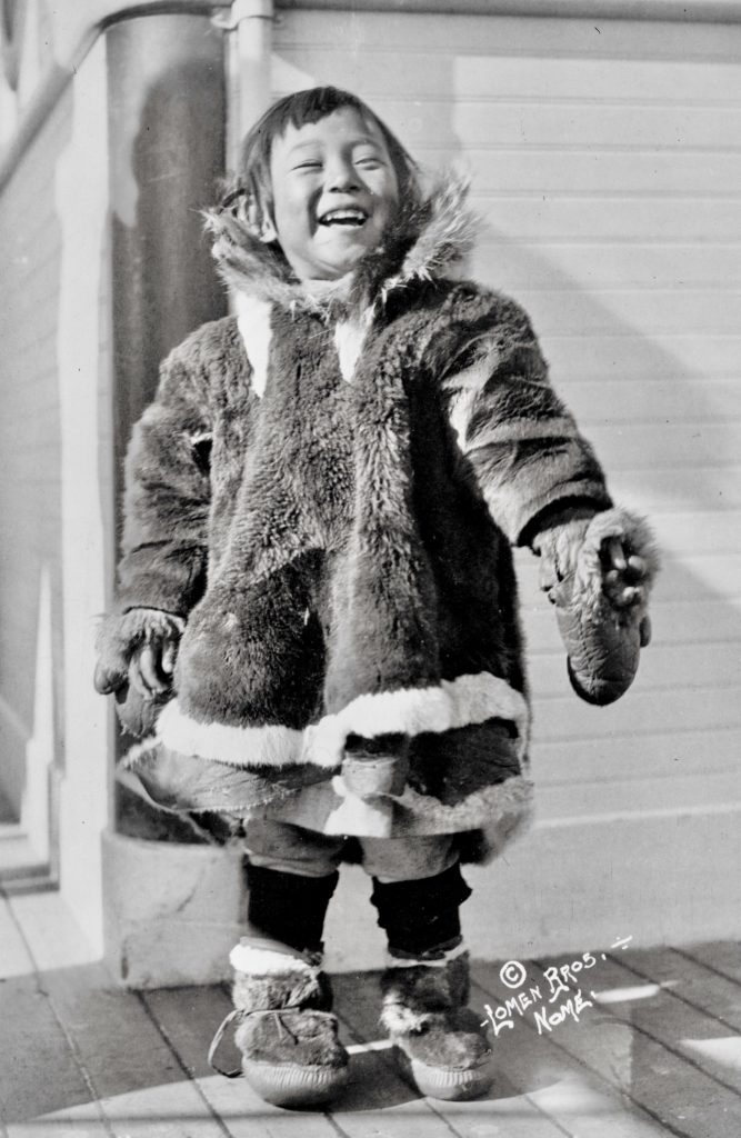 A three-year-old Inupiaq girl smiles at the camera while waring a parka