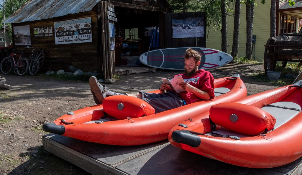 Young adult man sits in a red kayak reading