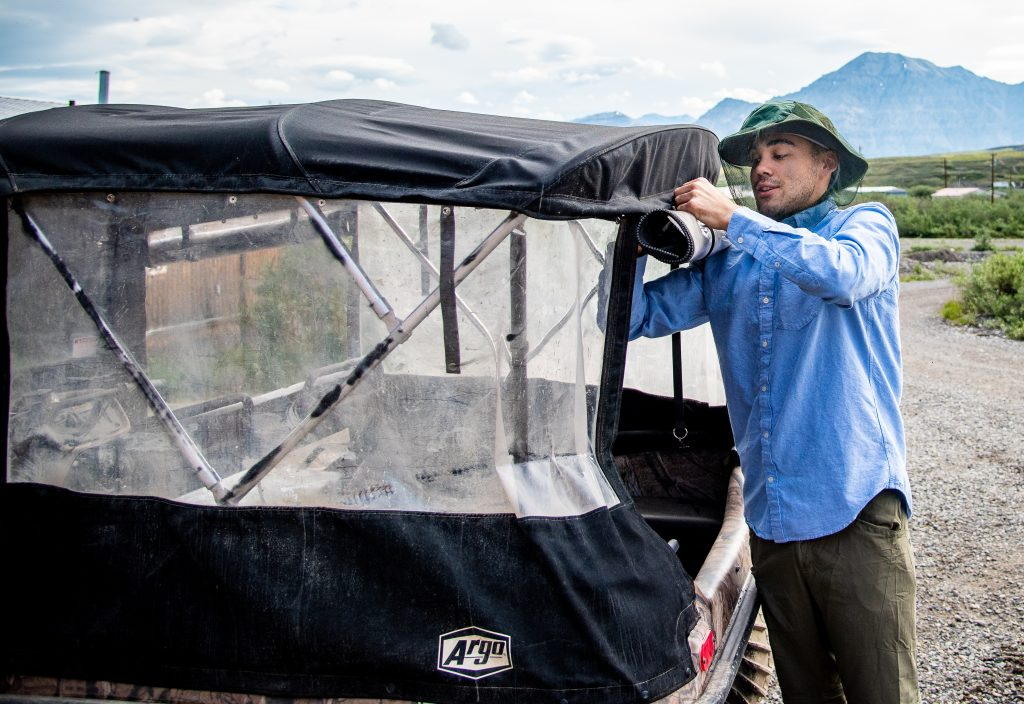 Man in blue shirt and bucket hat and mosquito net adjusts cover on an ATV
