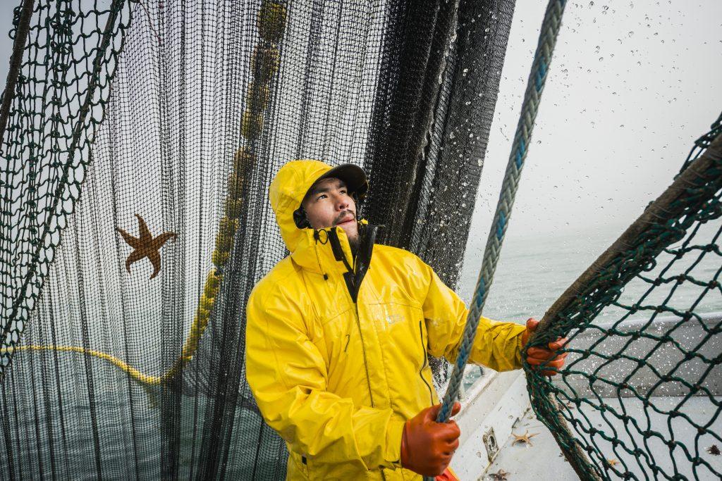 Fisherman in yellow gear pulls a net toward him