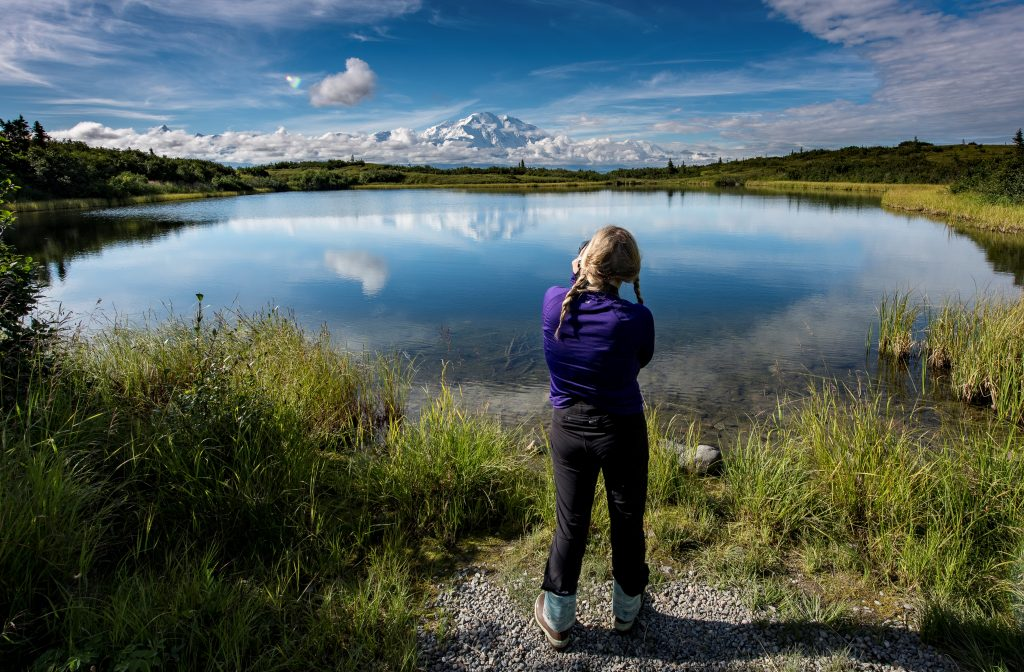 Woman takes a picture of Denali on a clear day with Reflection Pond in front of her.