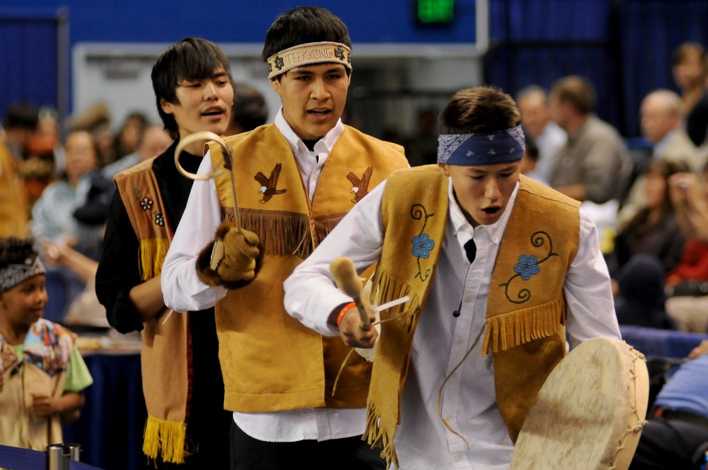 Three young Alaska Native men drumming during opening ceremonies in a gym