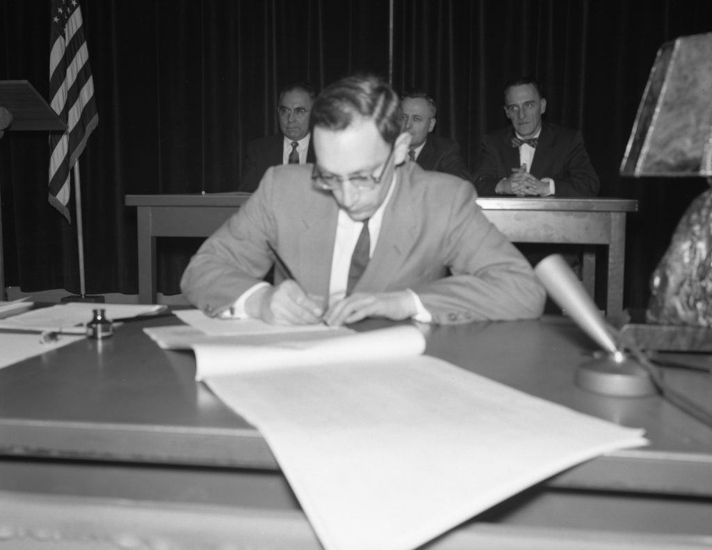 Young vic fischer in suit and tie signing Alaska constitution