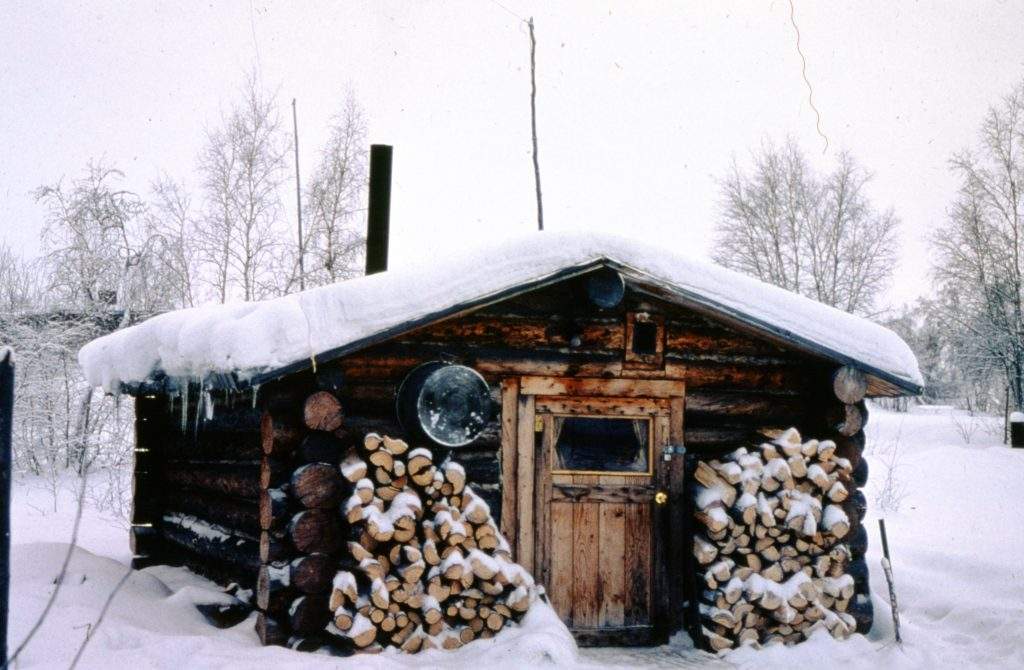 Small log cabin with snow on the roof and stacks of firewood outside