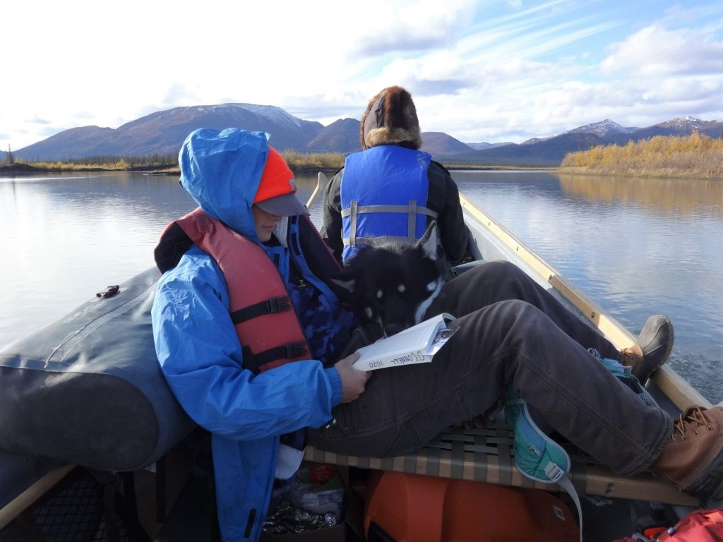 One passenger reads while another watches the water ahead while boating the junjik river