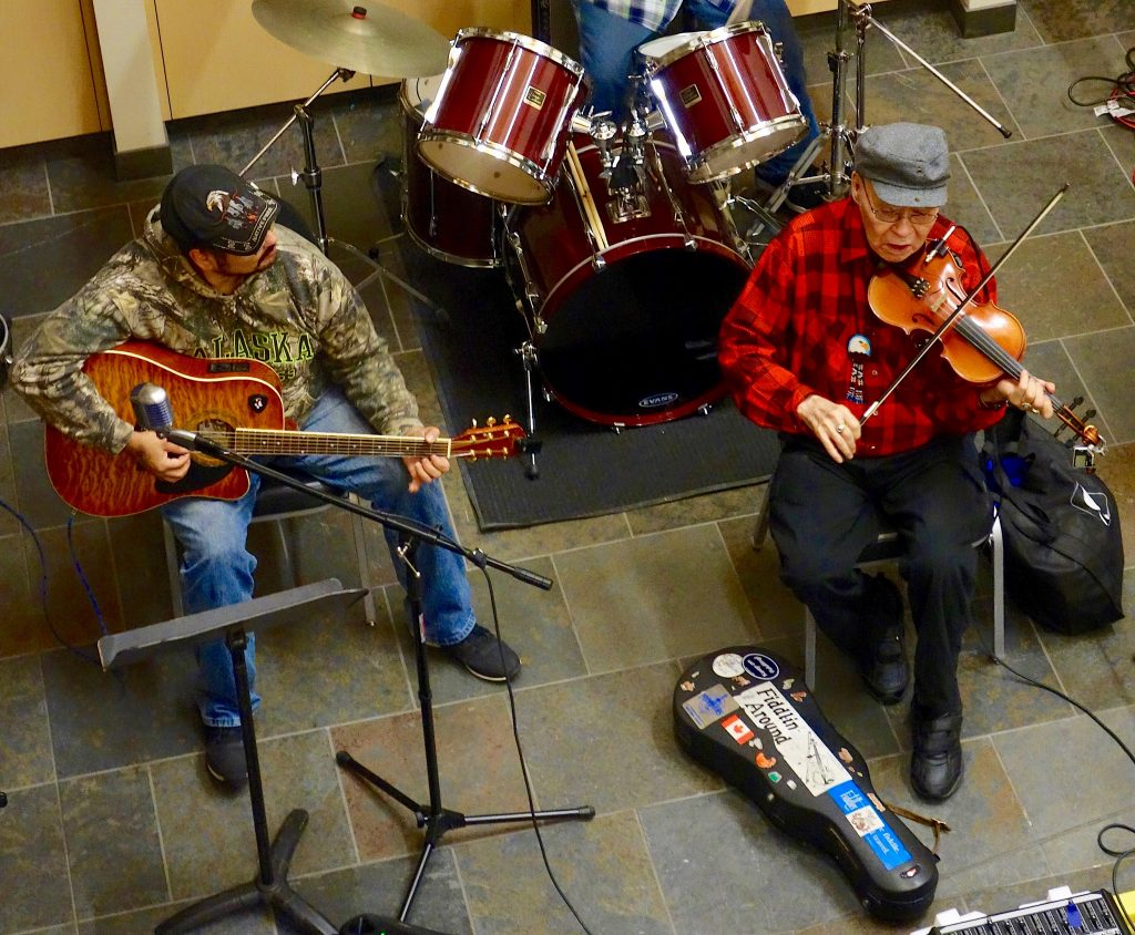 A small band plays, with an elder on fiddle, another player on guitar and a third on drums