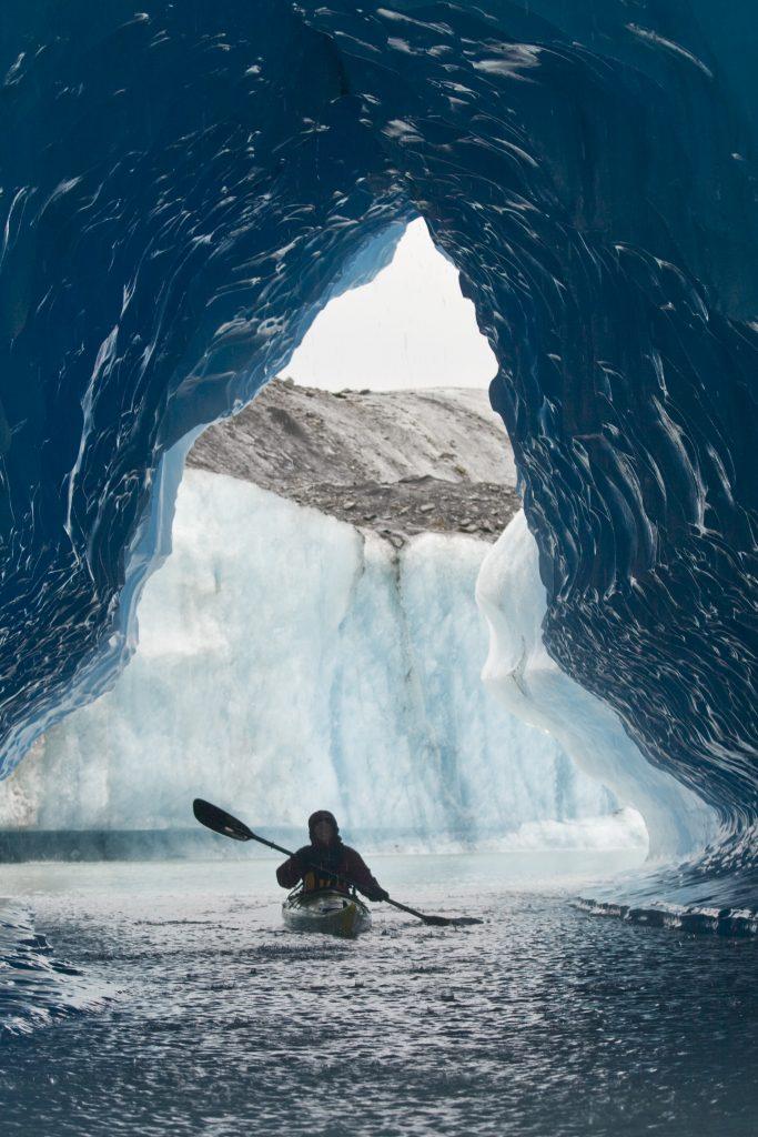 Kayaker through a tunnel in a glacier in Bear Glacier Lagoon, a hidden Alaska that promises adventure