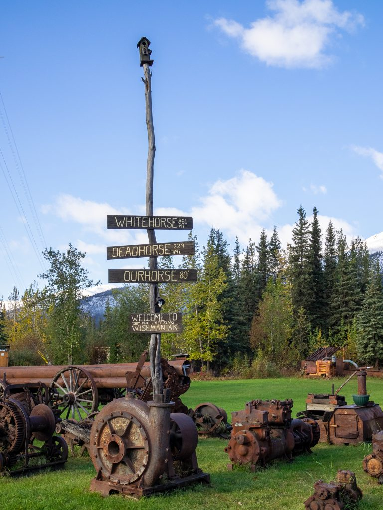 Stick with painted signs marking distance to whitehorse, deadhorse and ourhorse