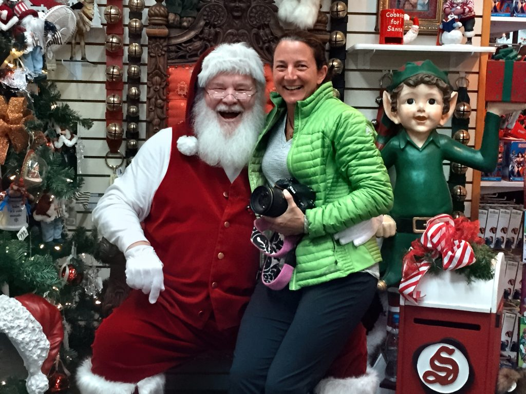 Author Michelle Theall sits on santa's lap while smiling and holding camera in North Pole, Alaska