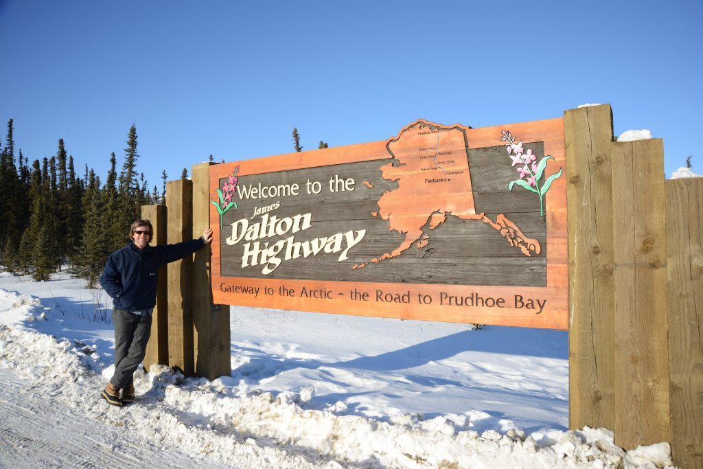 Person poses by Dalton Highway sign in the snow