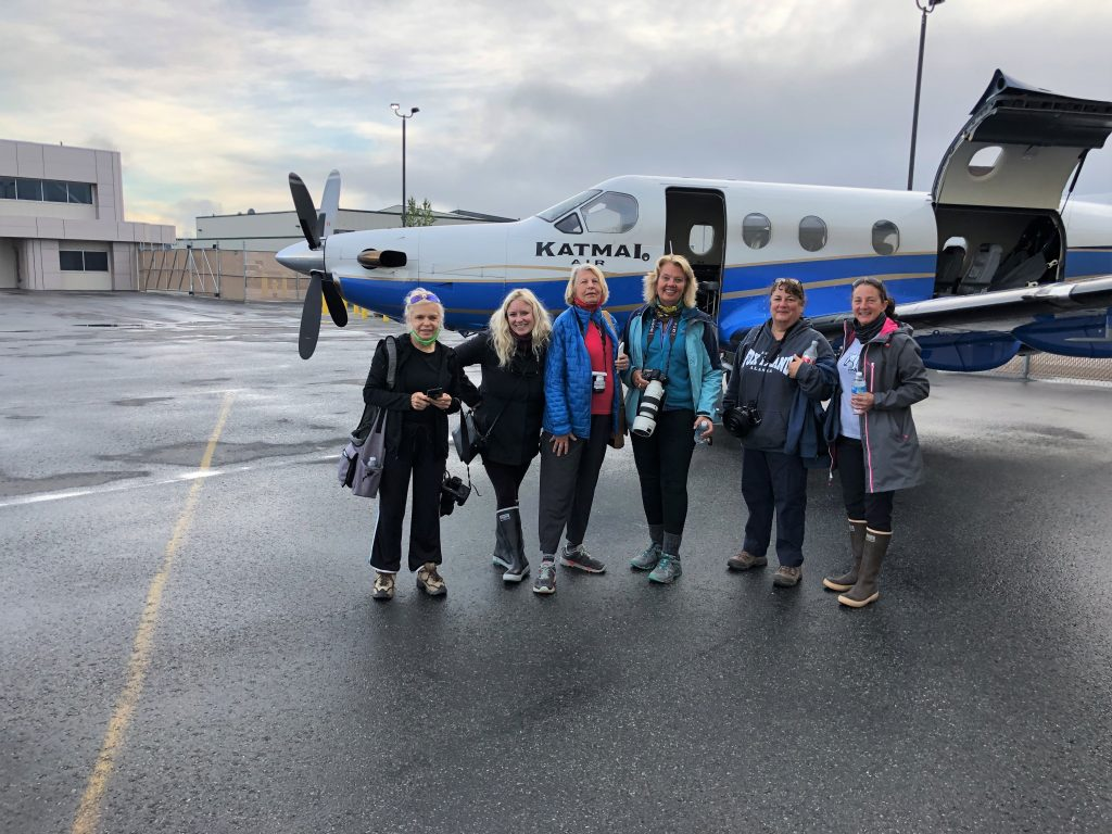 Group of six female photographers in front of small prop plane