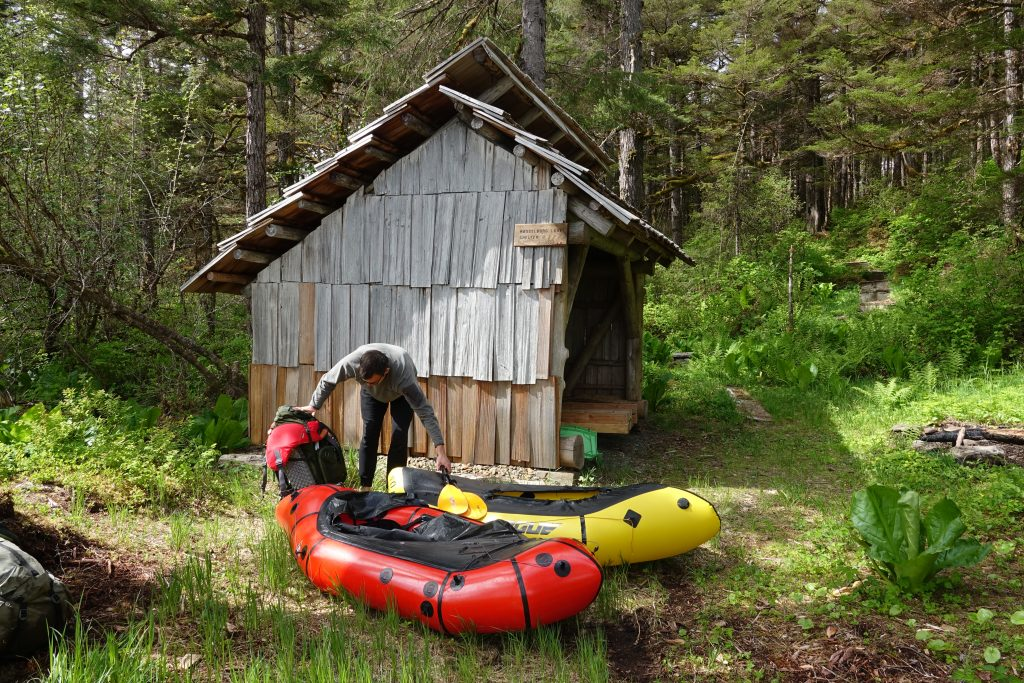 A man pulls up packrafts by a wooden three-sided shelter surrounded by trees on the Cross-Admiralty Island Canoe Route