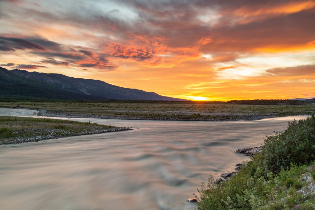 sunset lights up clouds orange and red over a forked river