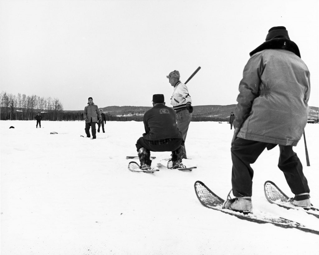 players stand in snow and play baseball while wearing snowshoes