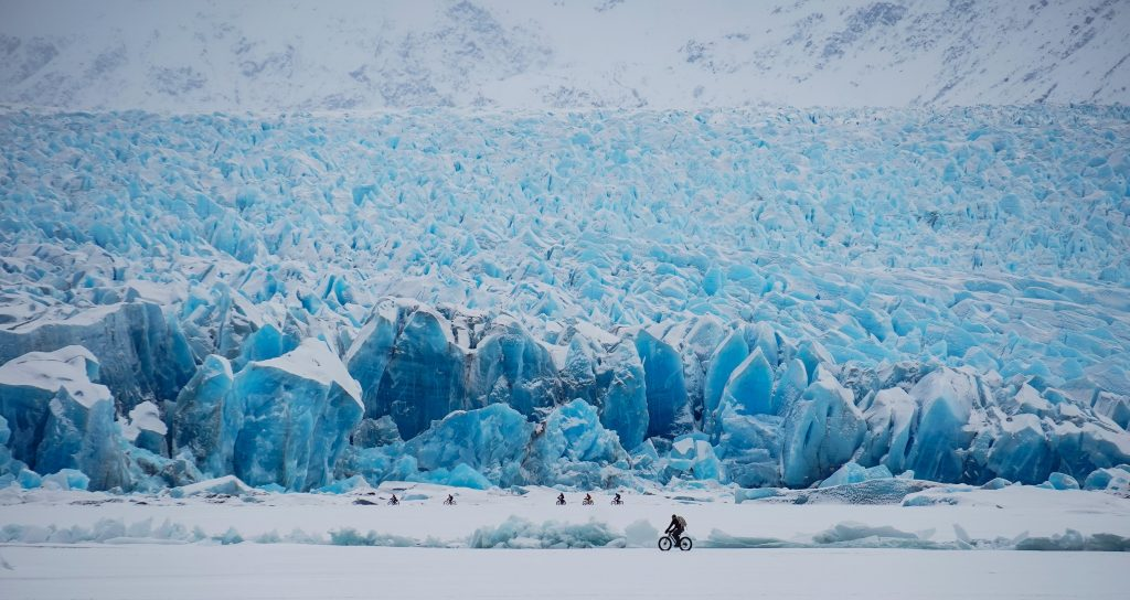 Fat-bikers bike across snow and ice at the toe of the Knik Glacier