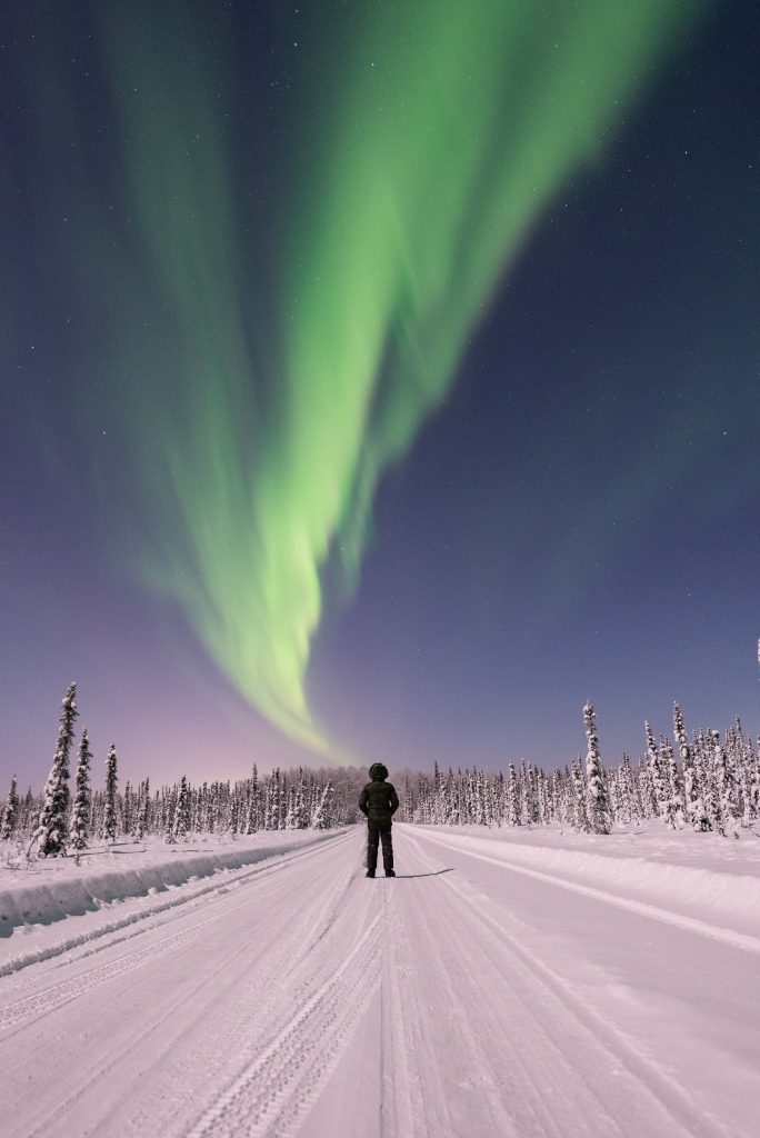 Small figure looks up at ribbon of green northern lights