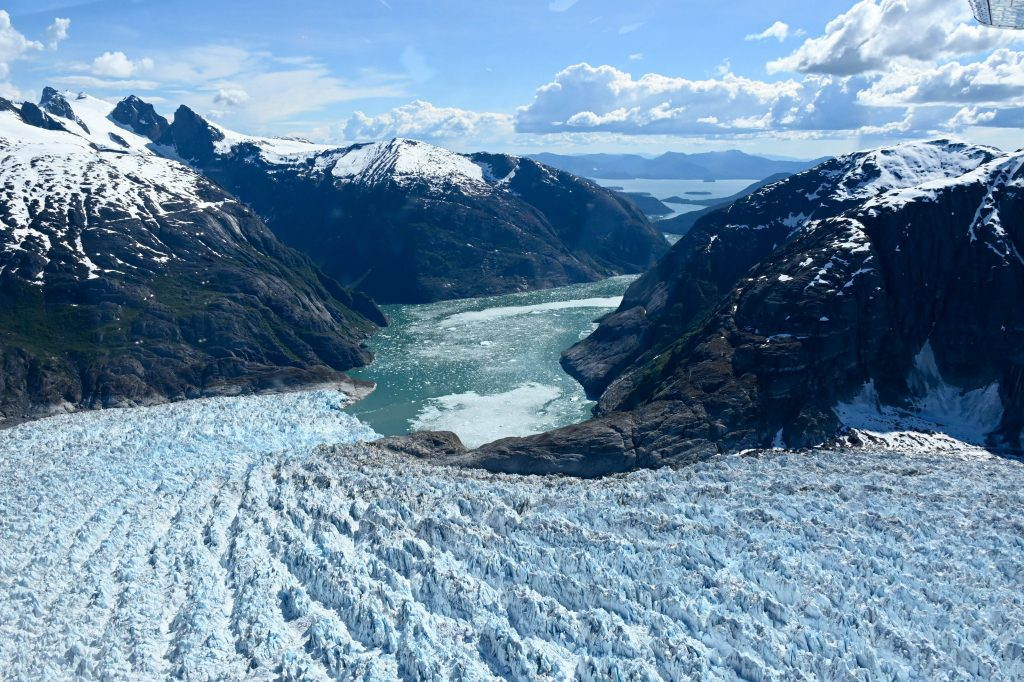 A glacier descends to bay surrounded by mountains in this aerial shot
