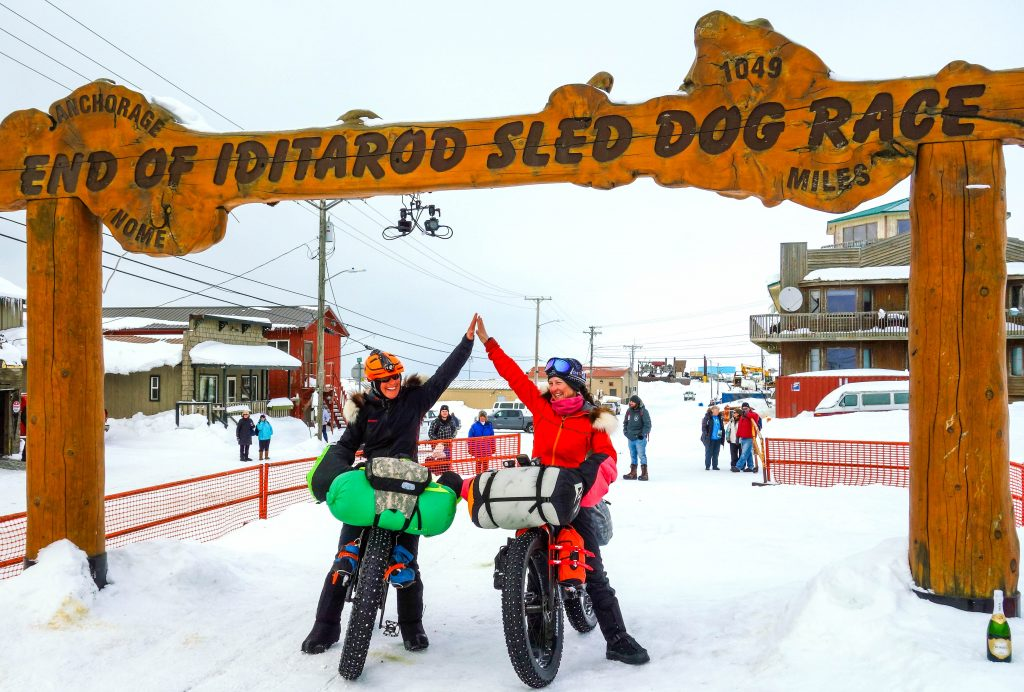 Two women on fatbikes high five under Iditarod arch in Nome