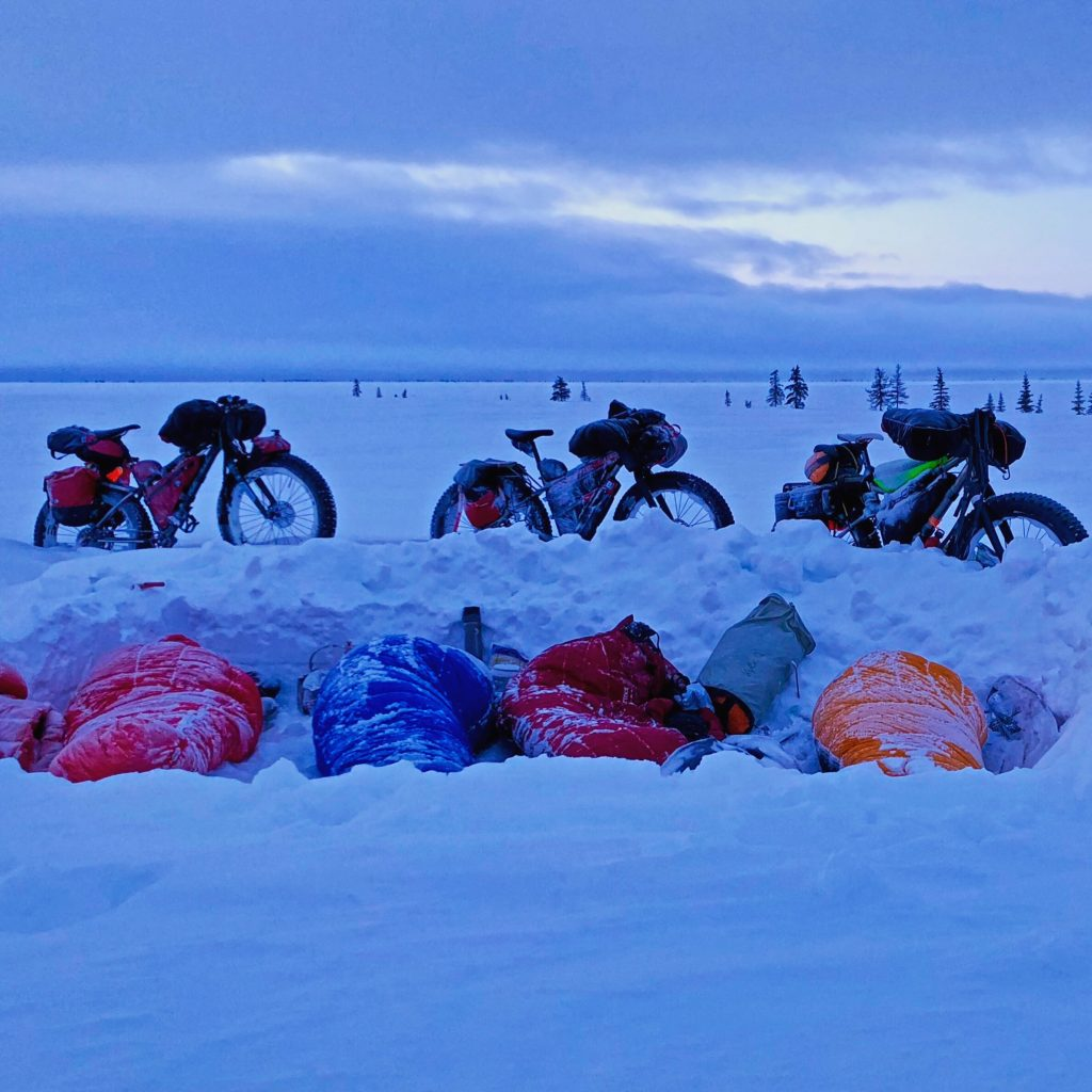 Sleeping bags in a trench behind snow drift and parked bicycles