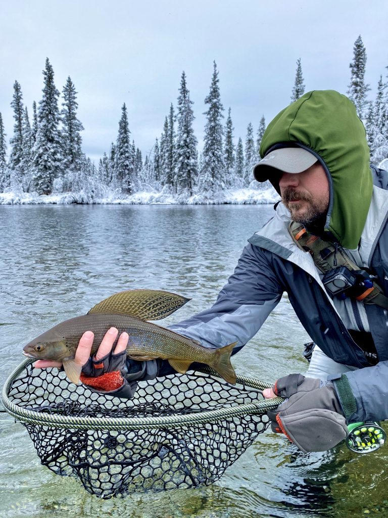 Jamie Moore holds a grayling above net in winter