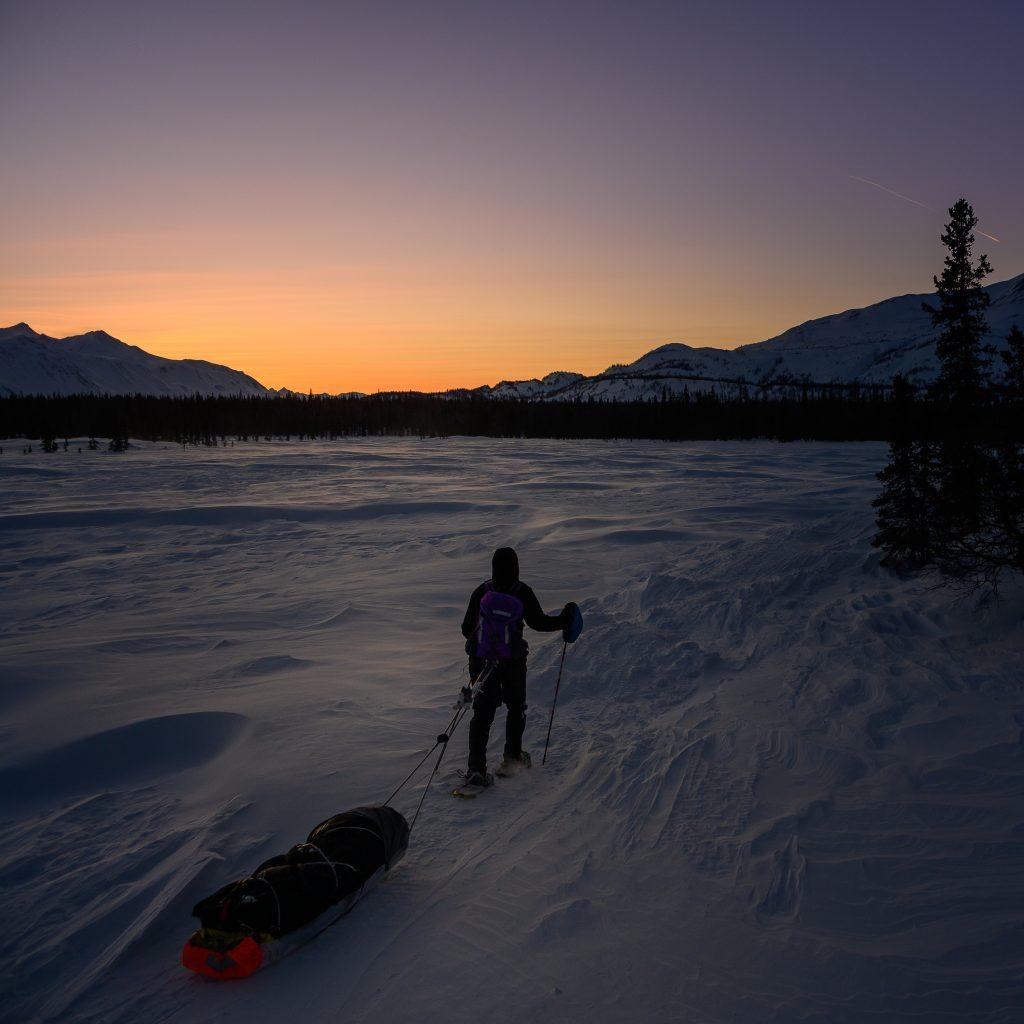 Skier hauling gear across snowy, frozen lake with glowing sunset