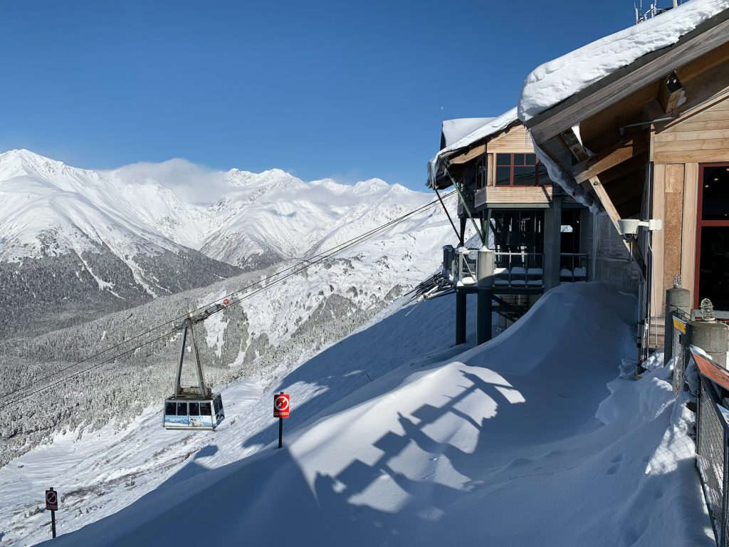 Tram moves above Alyeska's north face and snow covered mountains behind