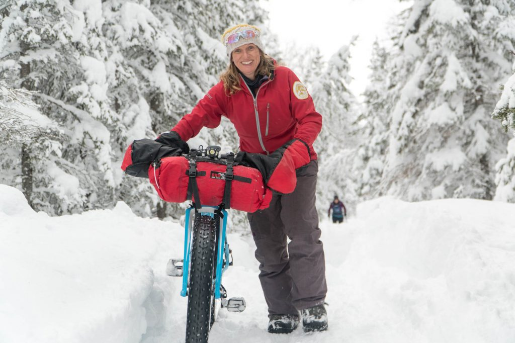 Kathi Merchant pushes a fat bike down a snowy tree-lined trail