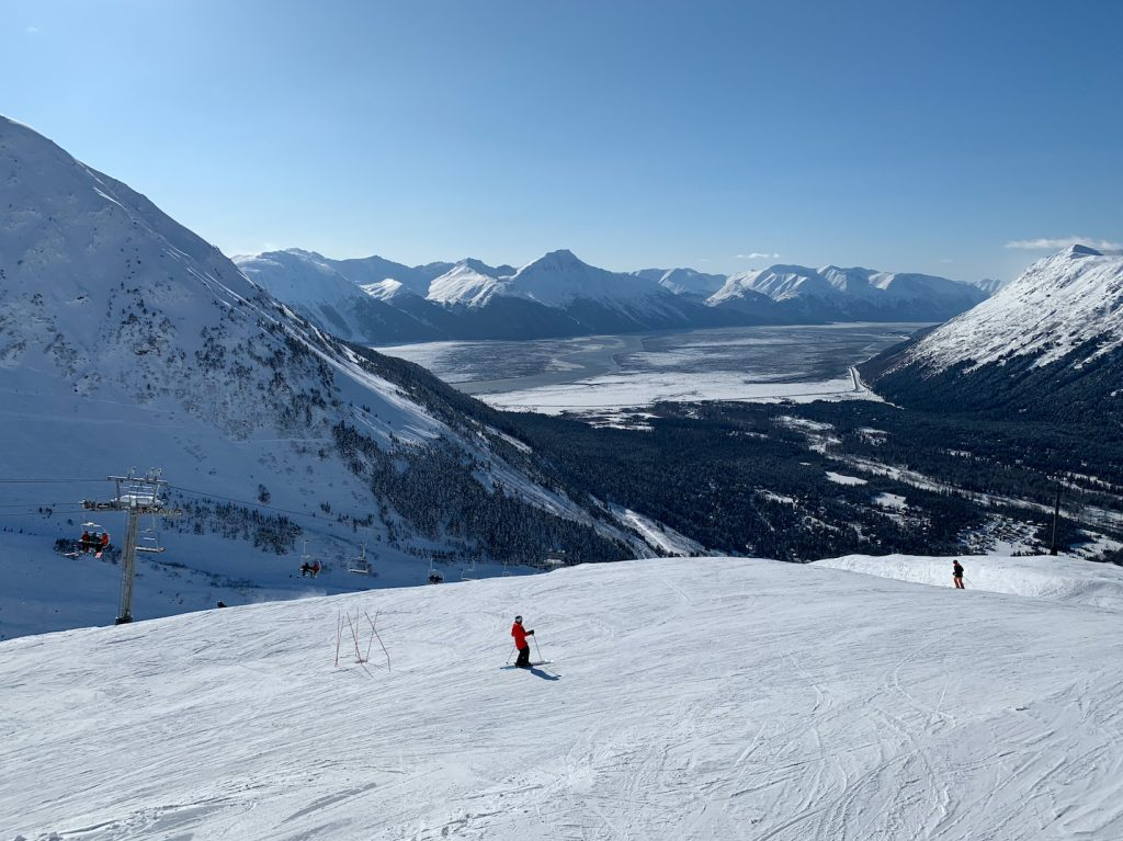 Skiers on groomed trail with scenic view of Turnagain Arm in distance