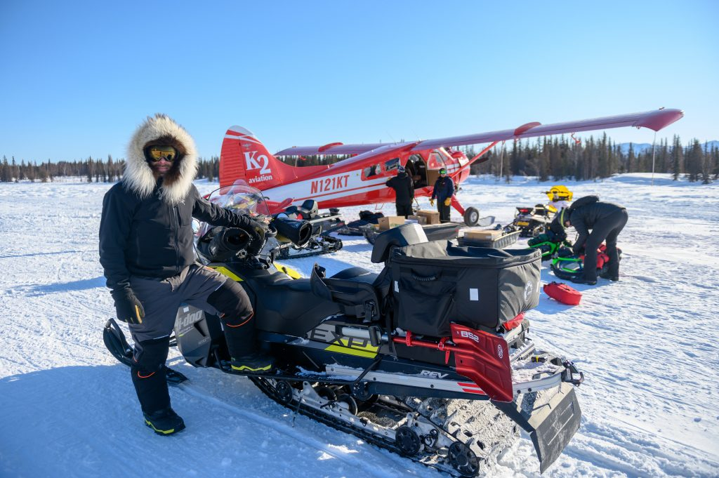 Iditarod Trail Invitational race director Kyle Durand by a snowmachine loaded with gear
