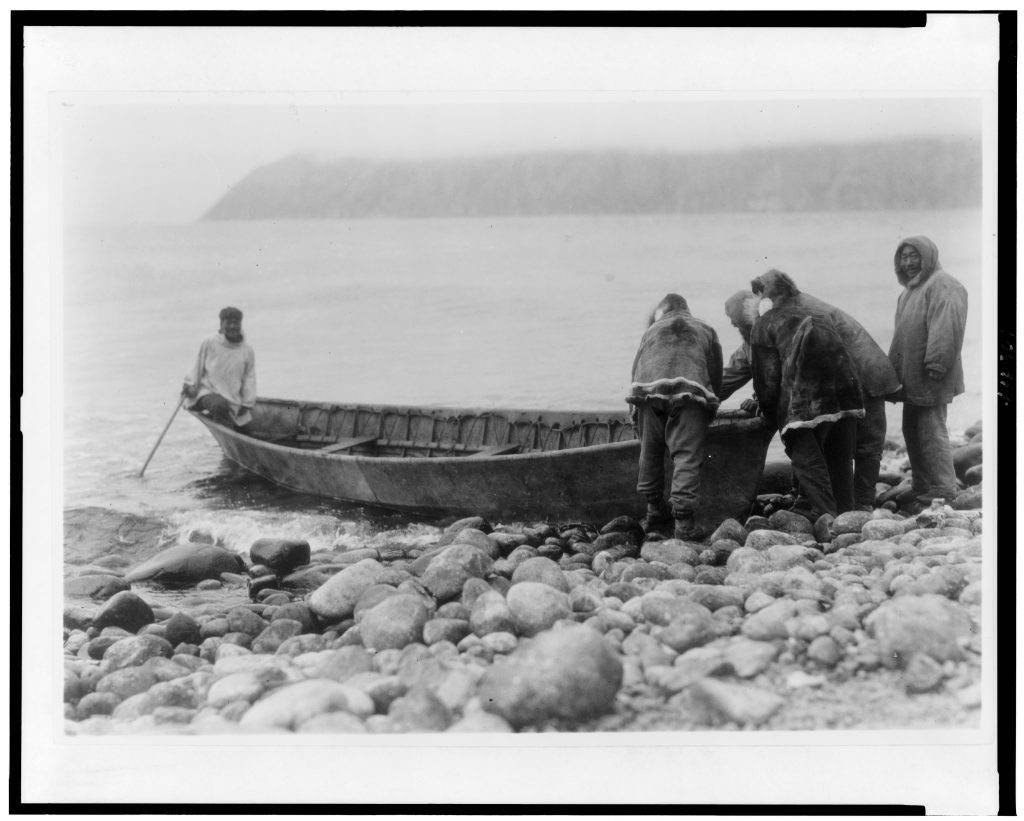 Black and White image men in parkas launching boat from rocky beach