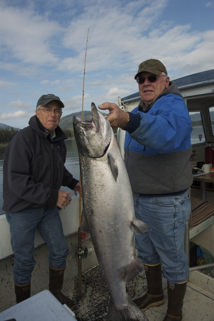 Two fishermen pose, one holding a king salmon by the gills