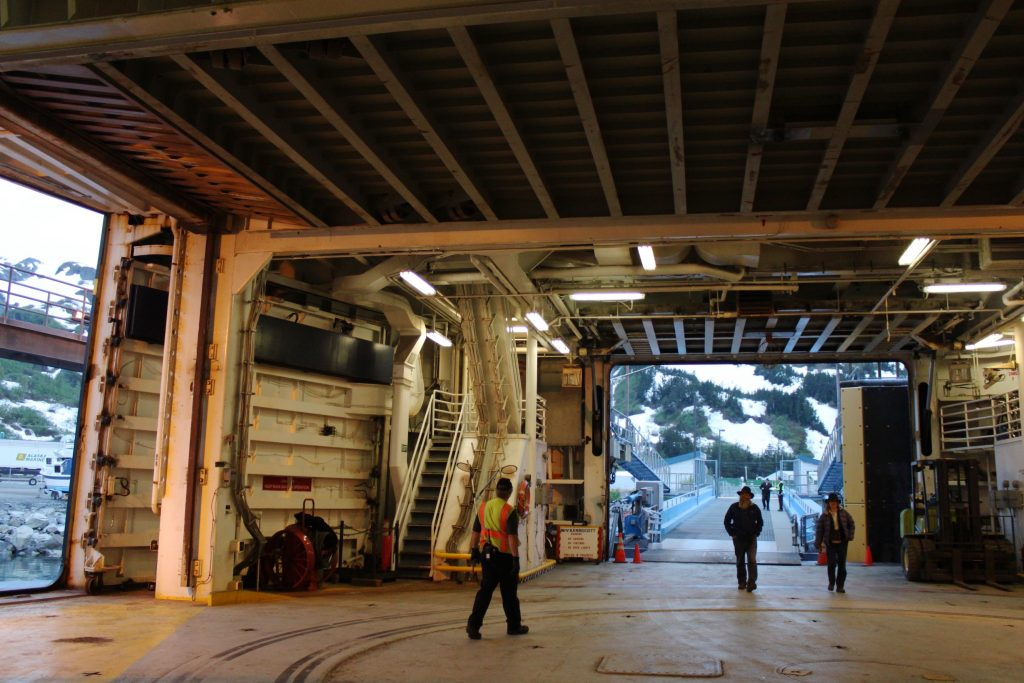 Passengers walk in car holding area of Alaska Marine Highway ferry
