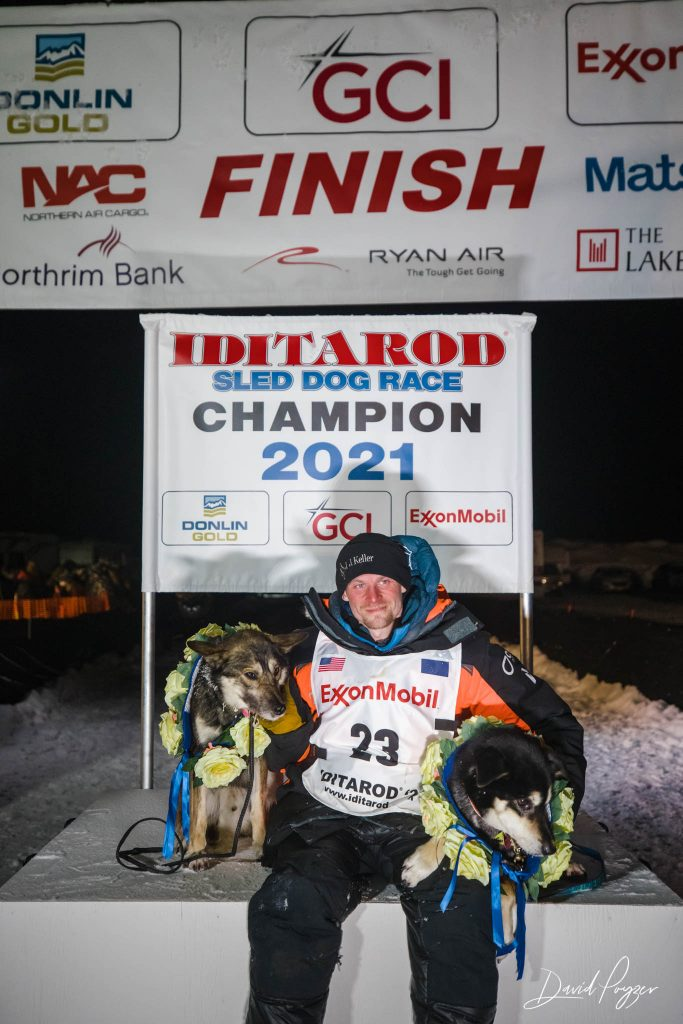 Iditarod musher Dallas Seavey with dogs under 2021 champion sign