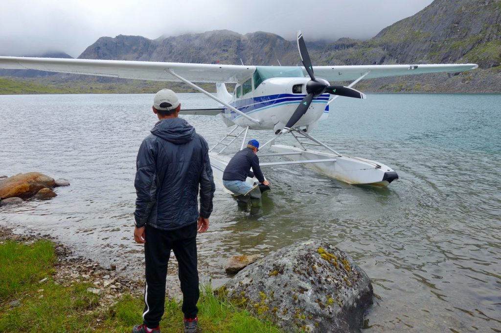 Man stands and waits for float plane arriving at the shore of a mountain lake